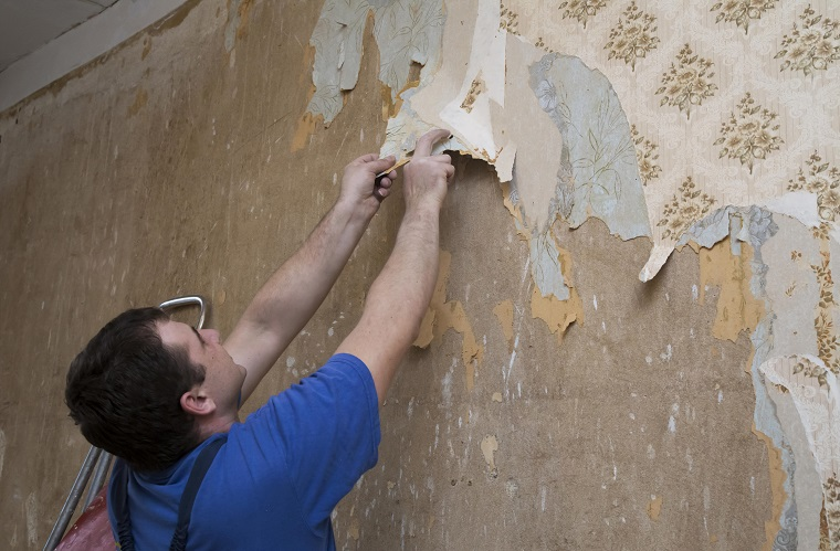 Tradesman is removing wallpaper